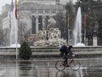 Un ciclista circulaba a las dos de la tarde de ayer junto a la estatua de la Cibeles durante la nevada.