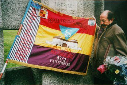 Enric Marco en 2003, cuando presidía la asociación Amical de Mauthausen, junto a una bandera alusiva a los exterminios nazis.