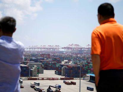 Dos hombres miran la zona de contenedores del puerto de Shanghái.