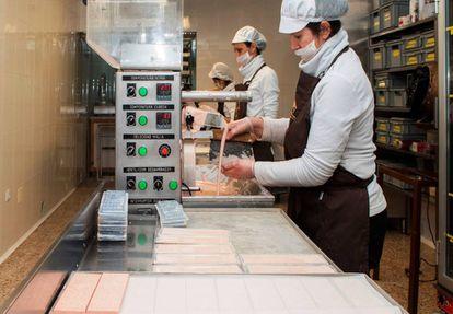 La emprendedora rural Isabel Félez, junto a dos de sus trabajadoras en su fábrica de chocolates artesanos en Alcorisa, un pequeño pueblo de Teruel.