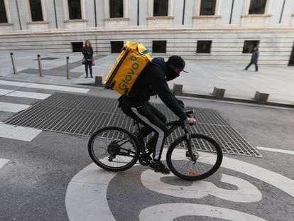 Un ciclista repartidor de Glovo por la Carrera de San Jerónimo de Madrid.