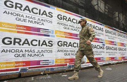 Un uniformado pasa frente a los carteles de agradecimiento del candidato presidencial Mauricio Macri que aparecieron este lunes en Buenos Aires.