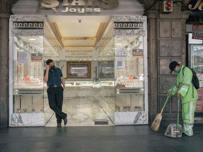Un trabajador municipal barre la acera junto a una joyería en Ciudad de México, en abril de este año.