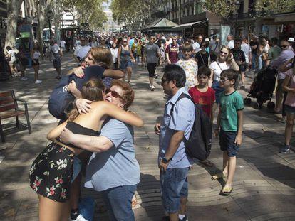 Dos jóvenes regalan abrazosa todas aquellas personas que se pasean por La Rambla de Barcelona.