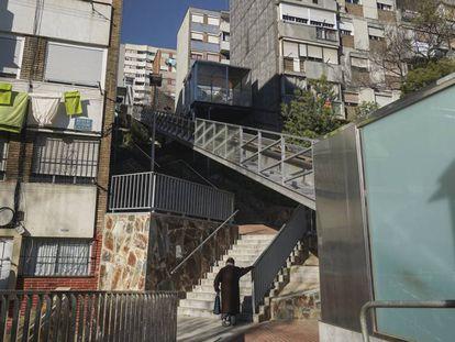 Una vecina sube por una escalera en la calle Calle Rasos de Peguera, en el barrio Ciutat Meridiana, en Barcelona.