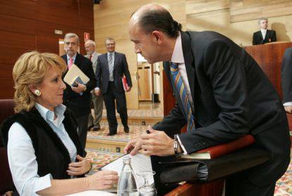 Aguirre habla con su entonces consejero de Sanidad, Manuel Lamela, en la Asamblea a finales de 2005.