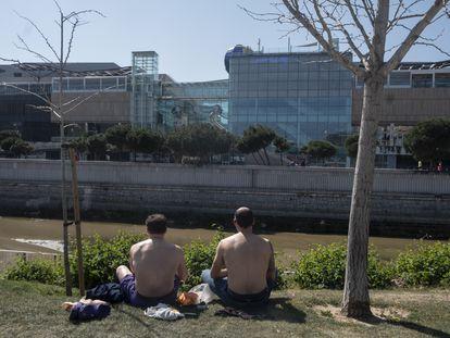 En la foto, dos chicos toman el sol en Madrid Río, este sábado.
