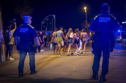 Una pareja de policías desaloja a un grupo de personas que permanecía en la calle tras el toque de queda en Barcelona.