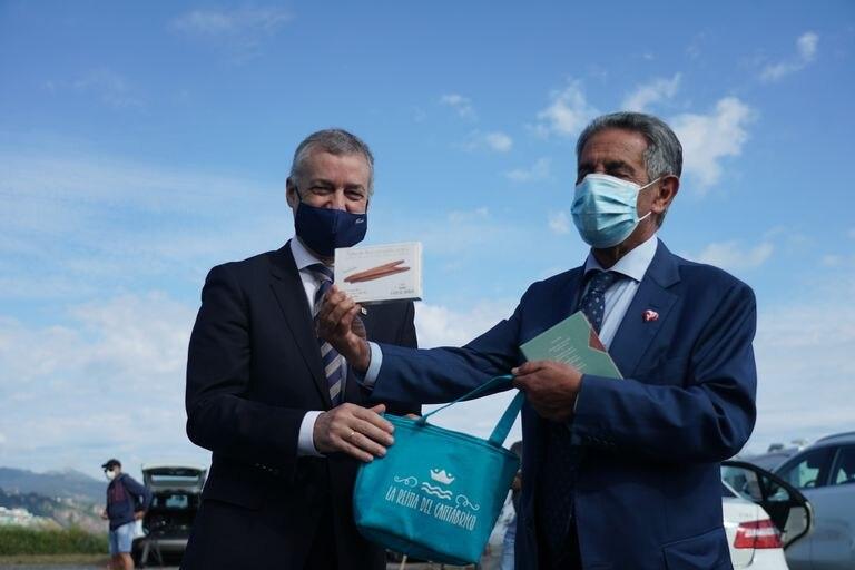 El presidente de Cantabria, Miguel Ángel Revilla, entrega al lehendakari, Íñigo Urkullu, anchoas de Santoña durante su encuentro en el barrio de Kobaron de la localidad vizcaína de Muskiz, el pasado viernes.