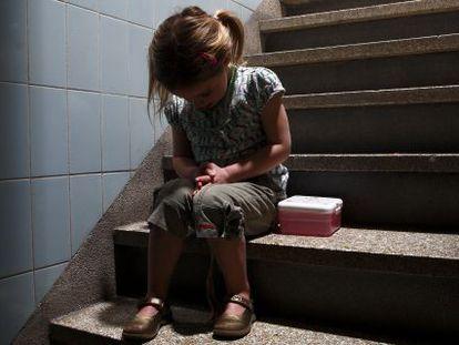 Una niña sentada en unas escaleras con la cabeza agachada y gesto de miedo