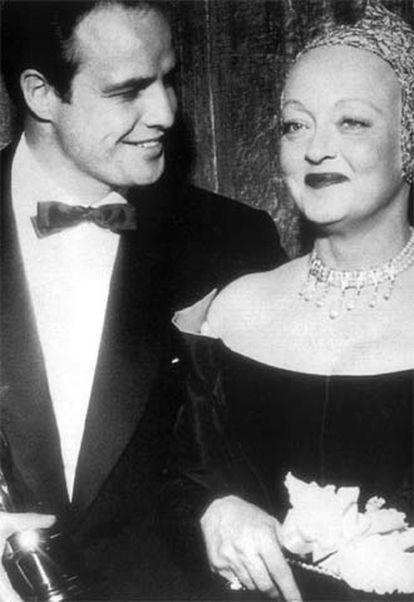 Marlon Brando, con el galardón al mejor actor por <i>La ley del silencio,</i> en 1955, junto a Bette Davis, quien le hizo entrega del premio.