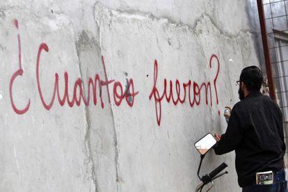 Un hombre pinta un muro durante el aniversario 25 de la invasión.
