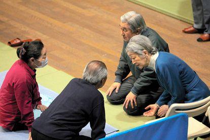 El emperador Akihito y su esposa Michiko conversan con una pareja en un centro para evacuados en Tokio. Se trata de la primera vez desde el terremoto del pasado 11 de marzo en el que matrimonio imperial  visita a los afectados.