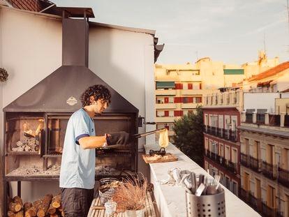 Pablo saca un queso fundido de su tradicional parrilla argentina, que ha instalado en el balcón de su apartamento en el centro de Madrid. La leña se carga en el brasero, y una vez que las ascuas caen al fondo, se colocan debajo de la parrilla principal.