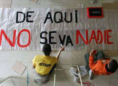 Unos niños pintan el lema de resistencia de la parroquia de San Carlos Borromeo, <i>De aquí no se va nadie,</i> extraído de un poema de León Felipe.