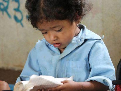 Una niña lee en su cuaderno en una escuela rural de Nepal.