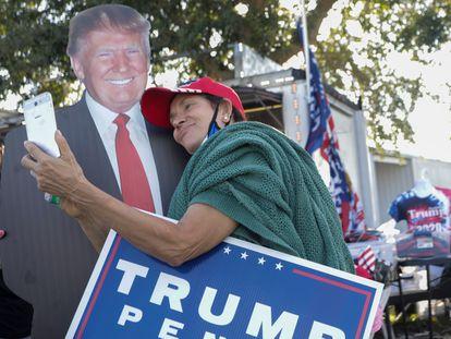 Una mujer se toma una foto con un cartel de Donald Trump en Orlando, Florida, este lunes.