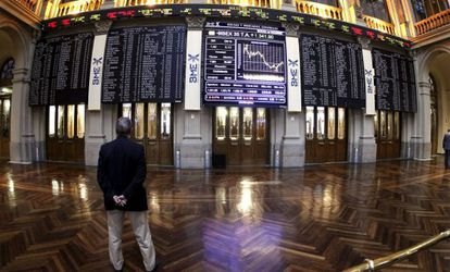 Un hombre mira los paneles de la Bolsa de Madrid
