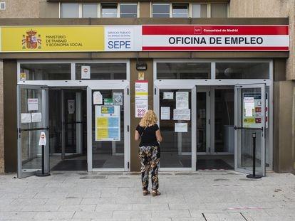 Una mujer a las puertas de una oficina del SEPE y una oficina de empleo de la Comunidad de Madrid.