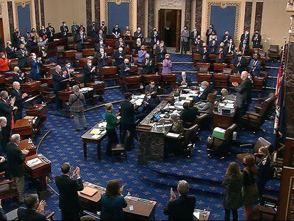 Los senadores aplauden el resultado final de la votación del plan de rescate, este sábado en Washington.