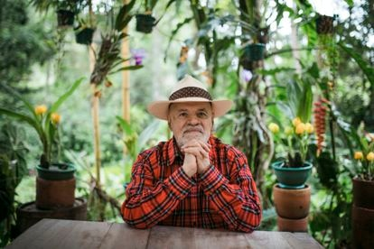 Guillermo Ángulo, rodeado de orquídeas, afuera de su casa en  Choachí, en el departamento de Cundinamarca.