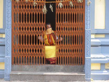 Un monje hindú mira desde el interior de un templo en India.