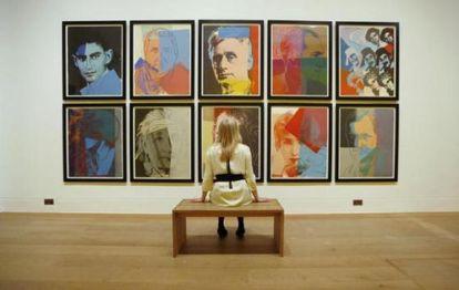 Una empleada de la galería Dulwich Picture de Londres observa la serie 'Diez retratos de judíos del siglo XX' de Warhol, en junio de 2012.