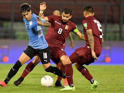 El futbolista venezolano Tomás Rincón (c) disputa el balón contra Facundo Torres de Uruguay, el pasado 8 de junio en Caracas.