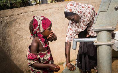 """En tan sólo cinco años, """"Khadi"""", como la llaman sus amigos, ha vivido en cinco lugares diferentes a causa de los conflictos armados o la sequía. Actualmente reside en el campo de refugiados de Daresalam, en la región del Lago Chad. En la foto, Khadija recoge agua junto a su hermana pequeña."""