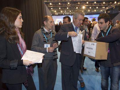 Atenea Chevillotte y un colaborador recogen encuestas de los compromisarios del PP en el congreso de Sevilla.