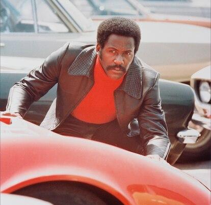 Richard Roundtree agachado detrás de un automóvil deportivo rojo en una escena de 'Shaft', 1971. La película blaxploitation, dirigida por Gordon Parks.