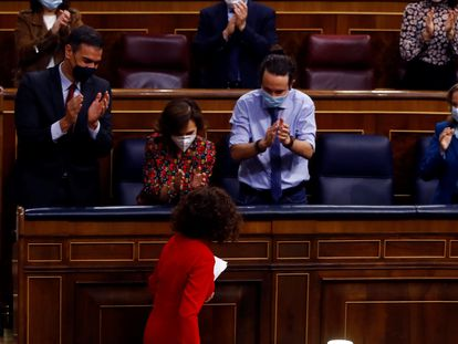 La ministra de Hacienda (de espaldas) es aplaudida por sus compañeros del Gobierno.
