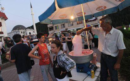 Dos niños esperan en un puesto de algodón de azúcar cerca de una mezquita reconstruida en julio de 2011 en Vlasenica, Bosnia.