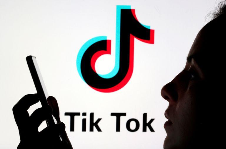 Una persona sostiene un teléfono móvil ante el logotipo de la red social china Tik Tok.