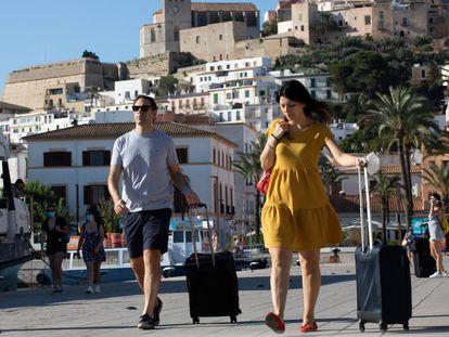 Dos personas con maletas caminan por Ibiza, el pasado 26 de junio.