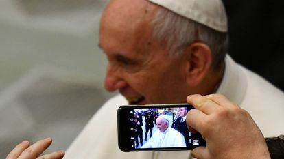 Una persona toma una foto del papa Francisco con un teléfono móvil.