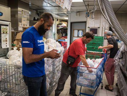 Kamel Guemari (izquierda), antiguo empleado de McDonald's, prepara bolsas de comida para su distribución junto a dos voluntarios.