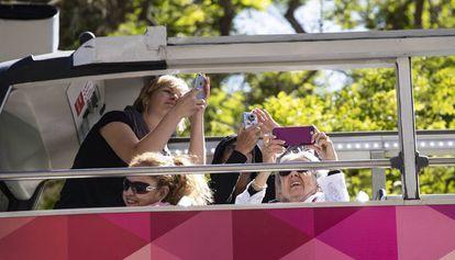 Turistas haciendo fotos desde un Bus Turístic.