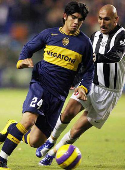 Banega se escapa de Guiñazú en un partido con Boca Juniors.