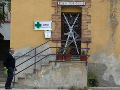 Un vecino pasea en Palomar de Arroyos (Teruel) frente a la farmacia cerrada por la Guardia Civil.