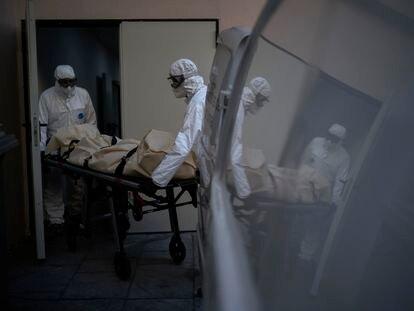 Dos trabajadores de una funeraria recogen un cadáver de una víctima de covid en una residencia en Barcelona, el 19 de noviembre.