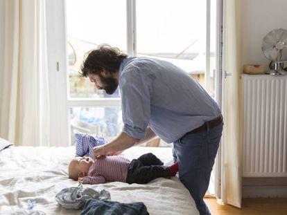 Un padre viste a su hijo.
