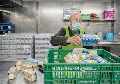 Basilio Carbonero, el voluntario más veterano de la Botiga d'Aliments Solidaris de Sant Boi, mientras ordena alimentos.