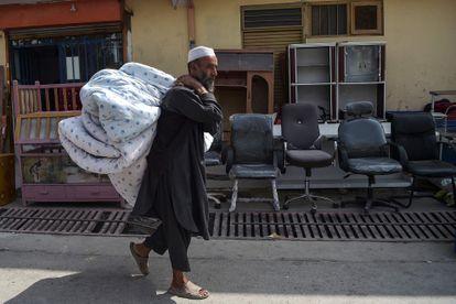 Un afgano acude al mercadillo de segunda mano del barrio de Khari Khana, en Kabul, para vender un colchón y su ropa de cama, el domingo.