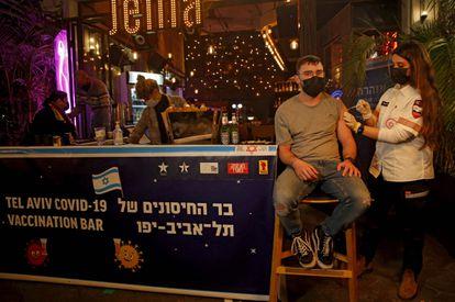 Una sanitaria administra una vacuna contra la covid en un bar de Tel Aviv.
