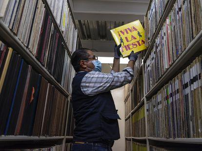 Un empleado encargado de resguardar los documentos sonoros de la Fonoteca Nacional de México saca un vinil de una estantería.