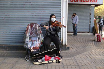 Una mujer toca el violín con su bebé en plena calle de una zona comercial de la capital.