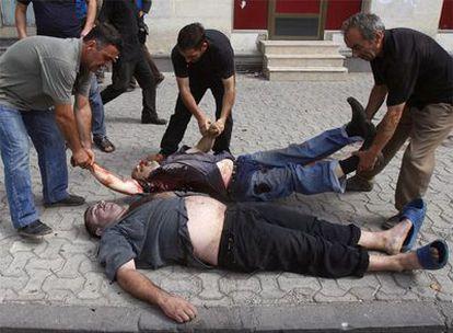 Varias personas recogen los cadáveres de dos hombres muertos durante un bombardeo ruso sobre Gori.