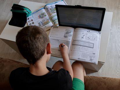 Un alumno de primaria hace los deberes de la asignatura de Inglés con varios libros y un ordenador.