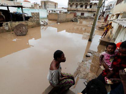 Una mujer habla con sus vecinos en una calle inundada en Ndiaga Mbaye, en el extrarradio de Dakar el pasado 6 de septiembre.